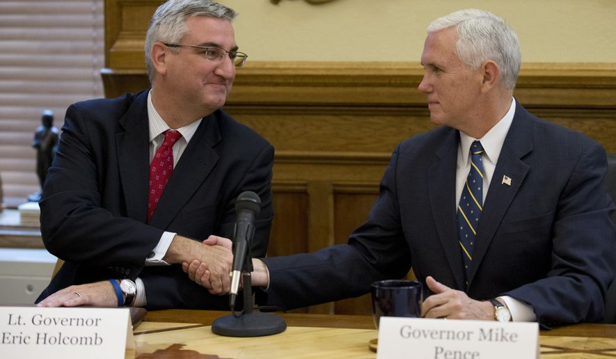 FILE - In this Nov. 14, 2016 file photo Vice President-elect Mike Pence, right, shakes hands with Indiana Governor-elect Eric Holcomb, as they participate in a cabinet meeting in the governor's Statehouse office in Indianapolis. Holcomb's inauguration as Indiana governor on Monday, Jan. 9, 2017, will complete a whirlwind ascension in the past year from a virtually unknown candidate to the state's top office. (AP Photo/Michael Conroy, File)