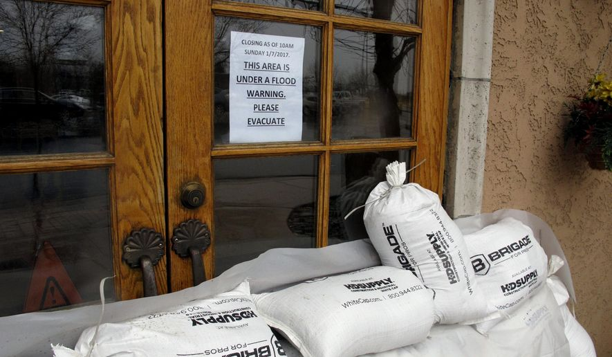 Sandbags line the doors of the Alamo truck stop and casino along U.S. Interstate 80 due to flooding Sunday, Jan. 8, 2017 in Sparks, Nev. More than 1,000 homes have been evacuated due to overflowing streams and drainage ditches in the area, which remains under a flood warning through Tuesday. (AP Photo/Scott Sonner)