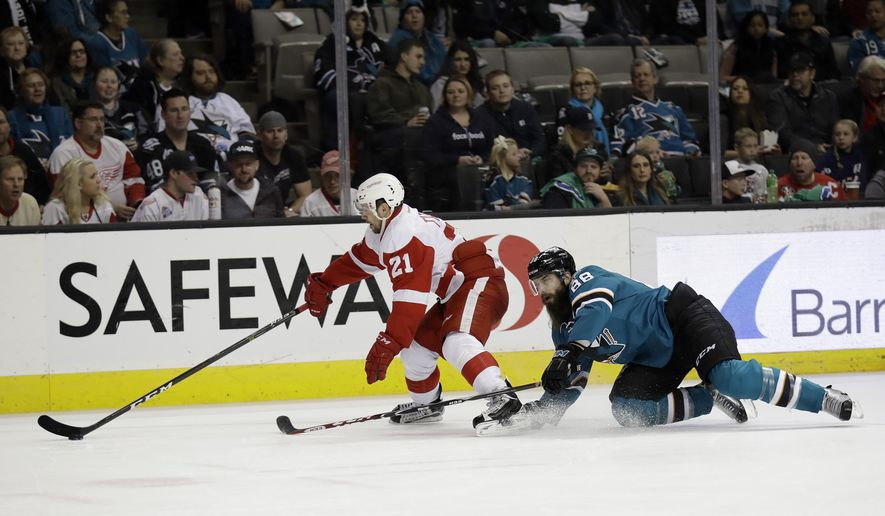 Detroit Red Wings' Tomas Tatar, left, is defended by San Jose Sharks' Brent Burns (88) during the first period of an NHL hockey game Saturday, Jan. 7, 2017, in San Jose, Calif. (AP Photo/Marcio Jose Sanchez)