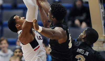 Central Florida's Chad Brown, center, blocks a shot-attempt by Connecticut's Vance Jackson, left, as Central Florida's A.J. Davis, right, also defends in the first half of an NCAA college basketball game, Sunday, Jan. 8, 2017, in Hartford, Conn. (AP Photo/Jessica Hill)