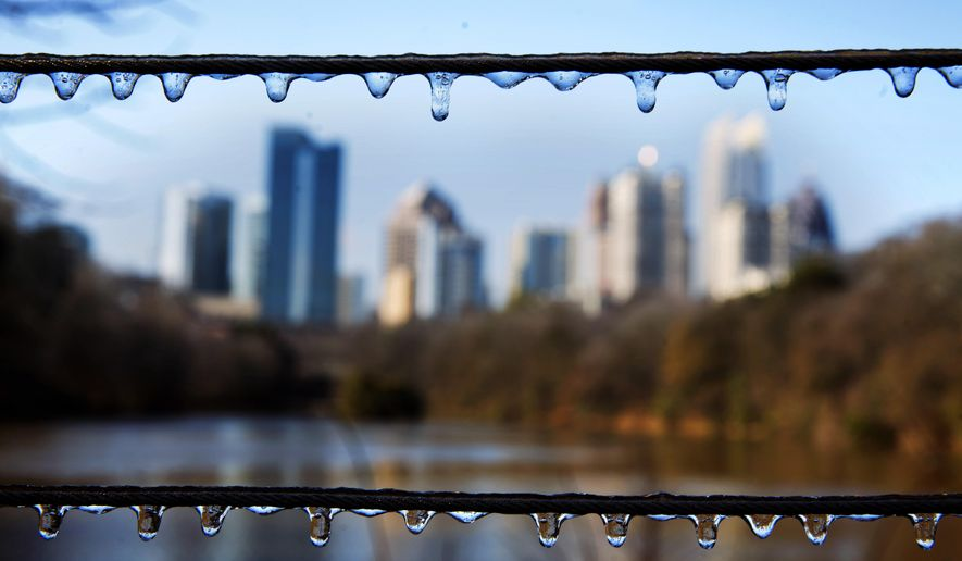 Ice covers a fence in Atlanta's Piedmont Park as the Midtown skyline stands in the background after a winter storm passed through on Saturday, Jan. 7, 2017. (AP Photo/David Goldman)