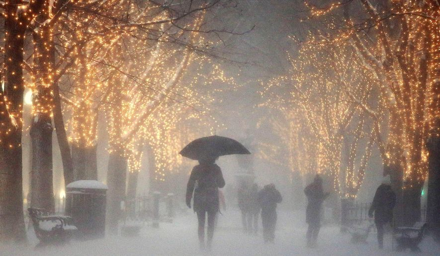 People walk through the Commonwealth Avenue Mall during a winter storm in Boston, Saturday, Jan. 7, 2017. A storm that wreaked havoc along the East Coast arrived in southern New England on Saturday, bringing blizzard conditions to some areas and making travel treacherous throughout the region. (AP Photo/Michael Dwyer)
