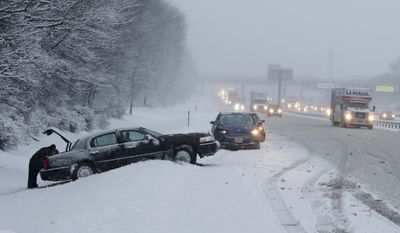 As traffic creeps past on the New Jersey Turnpike, drivers work on cars stuck in the snow Saturday, Jan. 7, 2017, near New Brunswick, N.J. (AP Photo/Mel Evans)