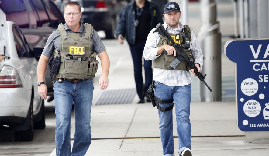 FBI agents walk outside the terminal at Fort Lauderdale–Hollywood International Airport, Friday, Jan. 6, 2017, in Fort Lauderdale, Fla. A gunman opened fire in the baggage claim area at the airport Friday, killing several people and wounding others before being taken into custody in an attack that sent panicked passengers running out of the terminal and onto the tarmac, authorities said. (AP Photo/Wilfredo Lee)