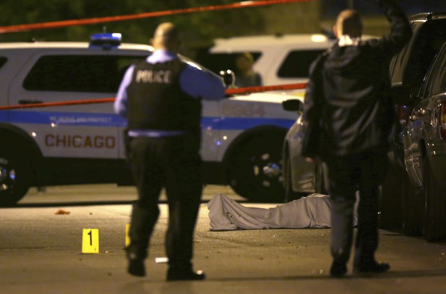 Police work the scene where a man was fatally shot in Chicago's Washington Park neighborhood on May 30, 2016. (Associated Press)