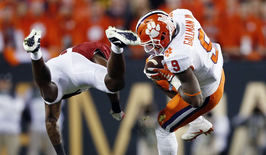 Clemson's Wayne Gallman tries to get past Alabama's Tony Brown during the first half of the NCAA college football playoff championship game Monday, Jan. 9, 2017, in Tampa, Fla. (AP Photo/John Bazemore)