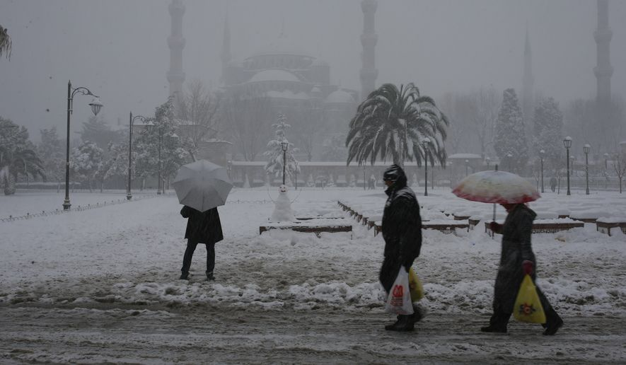 People walk during snowfall at Sultanahmet district, one of Istanbul's main tourist attractions, Monday, Jan. 9, 2017. Heavy snow clogged roads, and forced hundreds of flight cancellations in the Turkish metropolis. (AP Photos/Emrah Gurel)