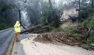 A Santa Clara County Roads and Airport Department worker responds to the scene of downed tree and mudslide on Summit Road in the Santa Cruz Mountains, Calif., Sunday, Jan. 8, 2017. Rivers are rising and winds are whipping up as a massive storm arrives in Northern California and is expected to push into Nevada by the evening. (Josie Lepe/Bay Area News Group via AP)