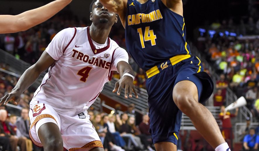 California guard Don Coleman (14) gets by Southern California forward Chimezie Metu (4) for a basket during the first half of an NCAA college basketball game, Sunday, Jan. 8, 2017, in Los Angeles. (AP Photo/Gus Ruelas)