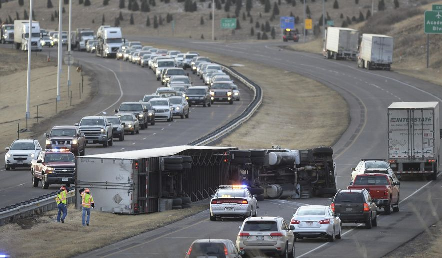 A rolled semi slows I-25 in the southbound lanes just north of the S. Academy Blvd exit Monday, Jan. 9, 2017, in Colorado Springs, Colo. High winds have overturned some large vehicles and damaged buildings in the Colorado Springs area while ice is making travel dangerous in western Colorado. (Mark Reis/The Gazette via AP)