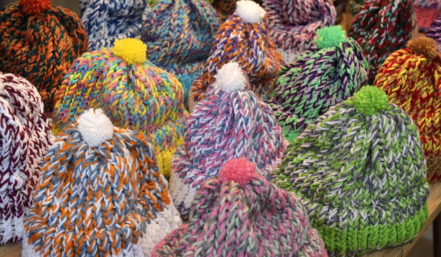 This Thursday, Jan. 5, 2017, photo shows caps recently knitted by Shelley Shellenberger, arranged in rows on a table at his apartment at Landis Homes in Lititz, Pa. Since the retired dairy farmer and Mennonite pastor learned to use the circular loom in 2007, Shellenberger has produced about 1,150 caps for needy adults and children in Eastern Europe, courtesy of Christian Aid Ministries in Ephrata, Pa. (Dan Marschka/LNP via AP)