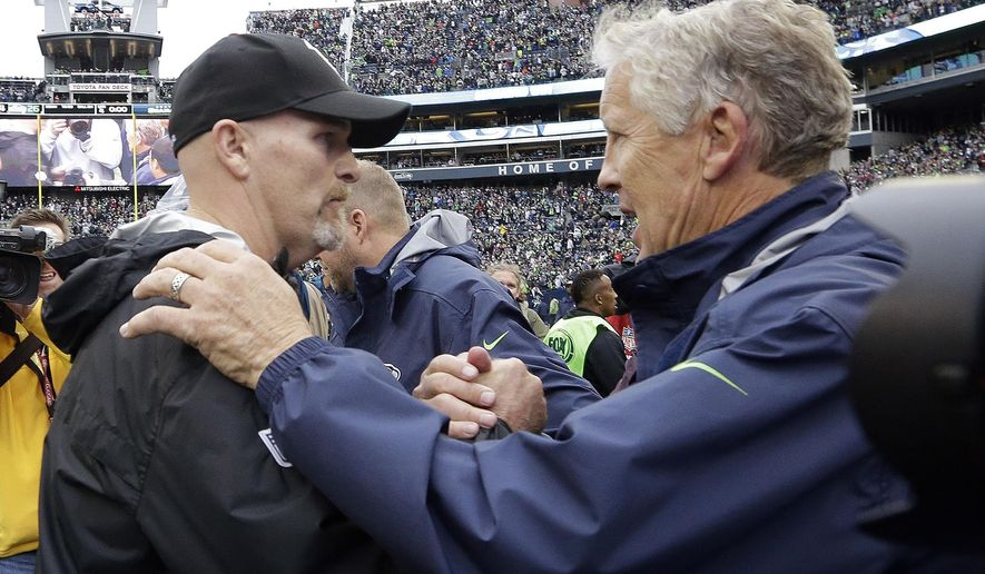 FILE - In this Oct. 16, 2016, file photo, Seattle Seahawks coach Pete Carroll, right, greets Atlanta Falcons coach Dan Quinn after an NFL football game in Seattle. Quinn and the Falcons play the Seahawks this week in the playoffs; Quinn is a former Seahawks defensive coordinator. (AP Photo/Elaine Thompson, File)