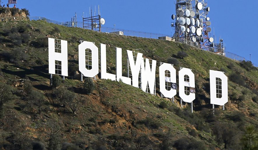 "FILE - In this Jan. 1, 2017, file photo, the famed Hollywood sign is seen altered to read ""HOLLYWeeD,"" in Los Angeles. Los Angeles police said in a statement that 30-year-old Zachary Cole Fernandez was arrested Monday, Jan. 9, 2017, in connection with the vandalism. Police say Fernandez turned himself in with his attorney and was booked on suspicion of misdemeanor trespassing. (AP Photo/Damian Dovarganes, File)"