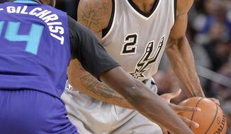 San Antonio Spurs forward Kawhi Leonard (2) looks to pass around Charlotte Hornets forward Michael Kidd-Gilchrist during the second half of an NBA basketball game, Saturday, Jan. 7, 2017, in San Antonio. San Antonio won 102-85. (AP Photo/Darren Abate)