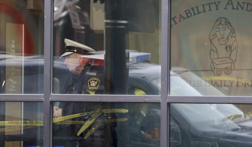 A Cincinnati police officer is seen through a window at Our Daily Bread Ministry in Over-the-Rhine in Cincinatti, Ohio, Monday, Jan. 9, 2017, after a Monday morning shooting.  A gunman at the social services mission in Cincinnati killed a man and critically wounded a woman at the facility Monday, police said. (Cara Owsley/The Cincinnati Enquirer via AP)