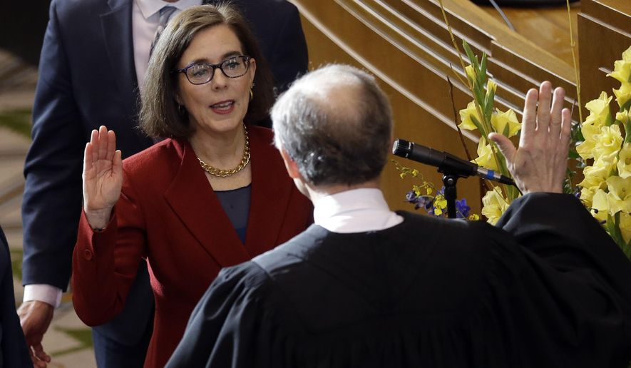 Oregon Gov. Kate Brown, left, is sworn in by Oregon Chief Justice Thomas A. Balmer in the Capitol House chambers in Salem, Ore., Monday, Jan. 9, 2017. Brown has been sworn in to complete the remaining two years of former Oregon Gov. John Kitzhaber's term. (AP Photo/Don Ryan)