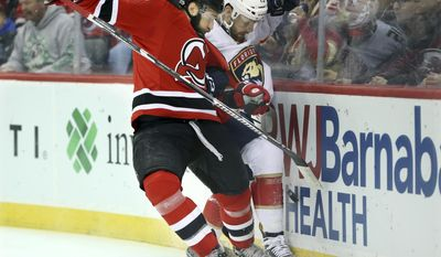 Jersey Devils defenseman Kyle Quincey (22) and Florida Panthers right wing Paul Thompson (15) collide over the puck during the first period of an NHL hockey game Monday, Jan. 9, 2017, in Newark, N.J. (AP Photo/Mel Evans)