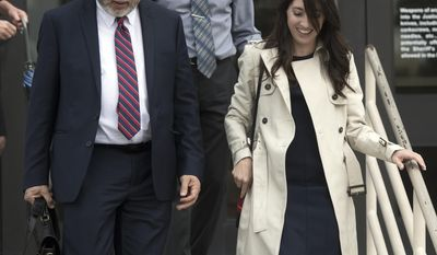 """Michelle Susan Hadley exits court with her attorney, Michael Guisti, left, and her father, Michael Hadley, after being cleared of all charges in a plot to frame her in Fullerton, Calif., Monday, Jan. 9, 2017. Hadley has been exonerated of charges that she placed """"rape fantasy"""" ads on Craigslist in order to get men to attack her ex-boyfriend's new wife. Prosecutors now say that it was the alleged victim in the case who was trying to frame her husband's ex by placing the malicious ads. (Jeff Gritchen/The Orange County Register via AP)"""