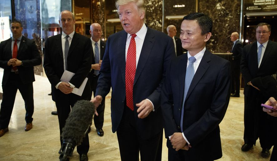 President-elect Donald Trump stands with Alibaba Executive Chairman Jack Ma as he speaks with reporters after a meeting at Trump Tower in New York, Monday, Jan. 9, 2017. (AP Photo/Evan Vucci)