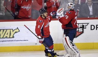Washington Capitals left wing Alex Ovechkin (8), of Russia, celebrates his goal with goalie Braden Holtby (70) during the third period of an NHL hockey game against the Minnesota Wild, Friday, Feb. 26, 2016, in Washington. The Capitals won 3-2. (AP Photo/Nick Wass)