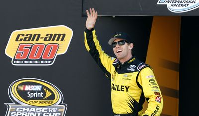 FILE - In this Nov. 13, 2016, file photo, Carl Edwards waves during driver introductions for the NASCAR Sprint Cup Series auto race at Phoenix International Raceway in Avondale, Ariz. Two people with knowledge of the situation tell The Associated Press that NASCAR driver Carl Edwards is retiring. Joe Gibbs Racing has scheduled a pair of news conferences Wednesday. Jan. 11, 2017, in which Edwards is expected to announce he is giving up the sport immediately. (AP Photo/Ralph Freso, File)