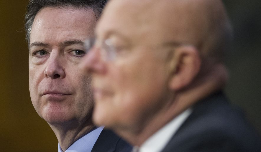 FBI Director James Comey listens at left as National Intelligence Director James Clapper testifies on Capitol Hill in Washington, Tuesday, Jan. 10, 2017, before the Senate Intelligence Committee hearing on Russian Intelligence Activities.  (AP Photo/Cliff Owen)
