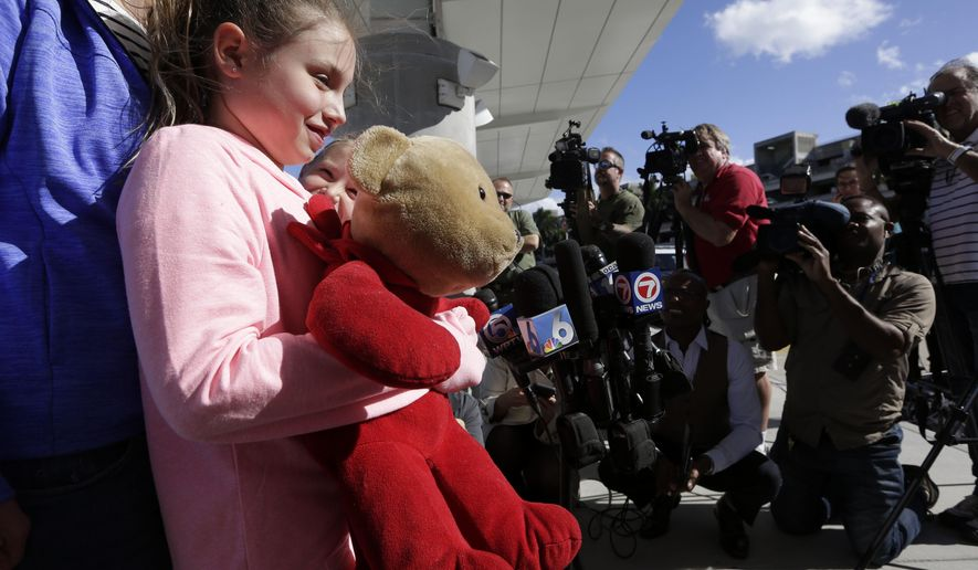 Courtney Gelinas talks with the news media after being reunited with her bear Rufus, at the Fort Lauderdale-Hollywood International Airport, Tuesday, Jan. 10, 2017, in Fort Lauderdale, Fla. Gelinas, of Windsor, Ontario, Canada, was traveling home with her family after a Caribbean cruise. They became separated from their belongings as they fled during last week's shooting at the airport in which five people were killed. (AP Photo/Lynne Sladky)