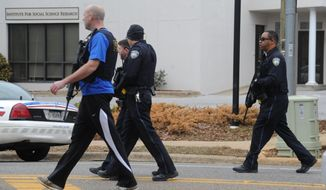 Law enforcement respond to the Alabama Credit Union on reports of a hostage standoff in Tuscaloosa, Ala., Tuesday, Jan. 10, 2017.  Lt. Teena Richardson, a Tuscaloosa police spokeswoman, told al.com that a gunman entered the building and took the employees inside hostage.    (Ben Flanagan/AL.com via AP)