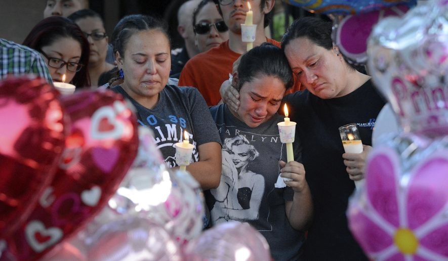 FILE - In this Aug. 25, 2016 file photo, from left to right, Nicole Maldonado, Myriah Flores, and her mother Sharlene Benavidez attend a candlelight vigil for 10-year-old Victoria Martens at the apartment complex, in Albuquerque, N.M., where the young girl lived and was killed. Martens was strangled to death on her 10th birthday before she was dismembered and her remains set on fire, according to an autopsy released months after police uncovered the sexual abuse they say she suffered at the hands of her mother and others leading up to her killing. (Jim Thompson  /The Albuquerque Journal via AP, File)