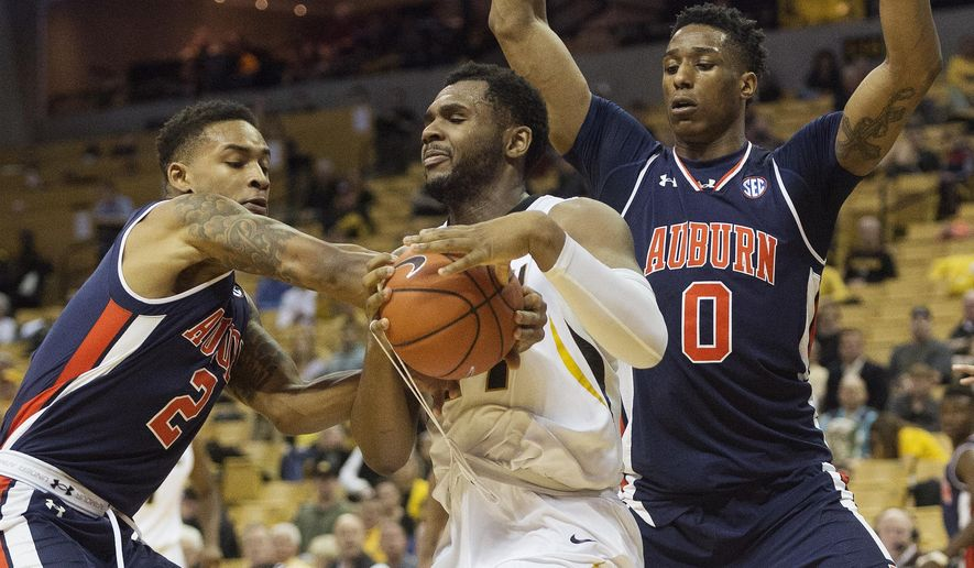 Missouri's Kevin Puryear, center, tries to hold on to the ball between Auburn's Bryce Brown, left, and Horace Spencer, right, during the first half of an NCAA college basketball game Tuesday, Jan. 10, 2017, in Columbia, Mo. (AP Photo/L.G. Patterson)