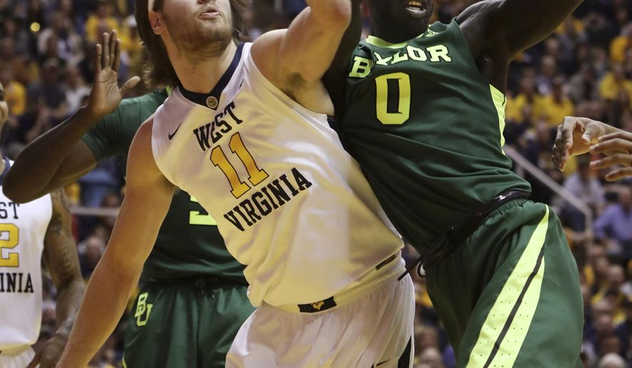 West Virginia forward Nathan Adrian (11) tries to steal the ball from Baylor forward Jo Lual-Acuil Jr. (0) during the first half of an NCAA college basketball game, Tuesday, Jan. 10, 2017, in Morgantown, W.Va. (AP Photo/Raymond Thompson)