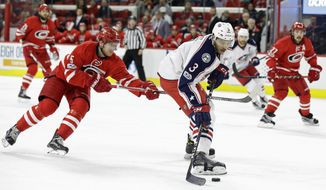 Carolina Hurricanes' Noah Hanifin (5) reaches as Columbus Blue Jackets' Seth Jones (3) controls the puck during the first period of an NHL hockey game in Raleigh, N.C., Tuesday, Jan. 10, 2017. (AP Photo/Gerry Broome)