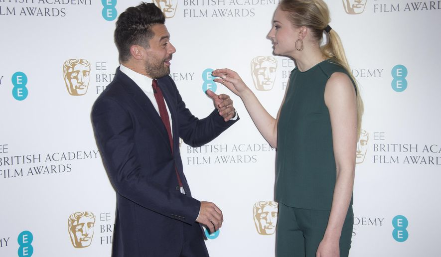 Actors Sophie Turner, right, and Dominic Cooper speak with each other before they pose for photographers after announcing the nominations for the EE British Academy Film Awards in 2017 at a photo call at BAFTA headquarters in central London, Tuesday, Jan. 10, 2017. (Photo by Joel Ryan/Invision/AP)