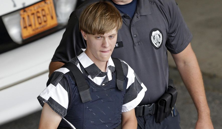 In this June 18, 2015, file photo, Charleston, S.C., shooting suspect Dylann Roof is escorted from the Cleveland County Courthouse in Shelby, N.C. A federal jury has sentenced Roof to death for killing nine black church members in a racially motivated attack in 2015. (AP Photo/Chuck Burton, File)