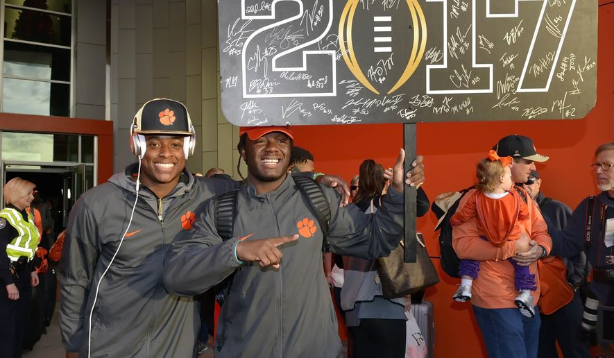 Clemson's Jalen Williams, right, and K'Von Wallace hold a sign after returning Tuesday, Jan. 10, 2017, in Clemson, S.C., the day after the Tigers defeated Alabama 35-31 in the College Football Playoff championship NCAA college football game in Tampa. (AP Photo/Richard Shiro)