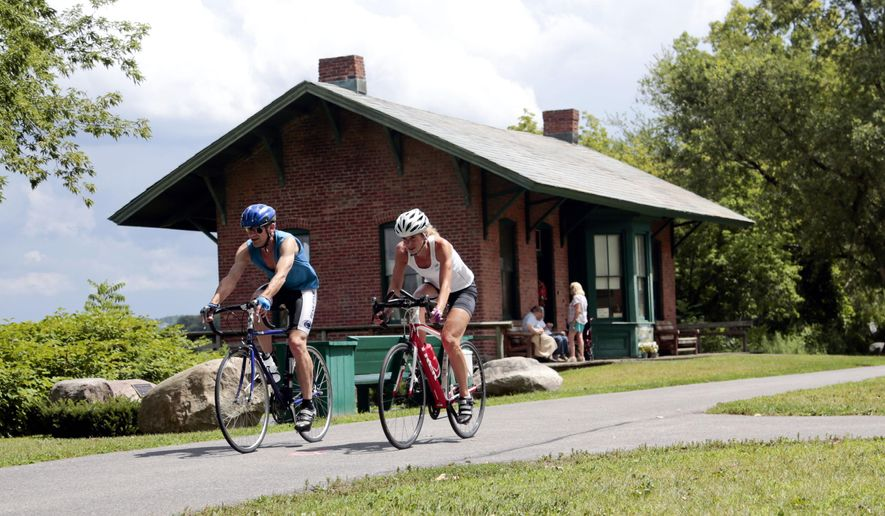 In this Tuesday, Aug. 4, 2015 photo, cyclists pass the Niskayuna Train Station as they bike on the Canalway Trail in Niskayuna, N.Y. Gov. Andrew Cuomo proposed a a 750-mile paved biking and hiking Empire State Trail, of which the Canalway Trail would be part of. (AP Photo/Mike Groll, File)