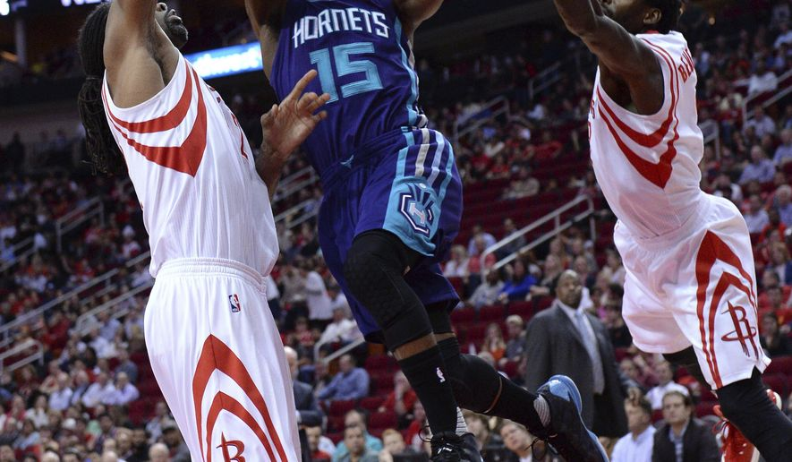 Charlotte Hornets guard Kemba Walker (15) shoots between Houston Rockets' Nene, left, and Patrick Beverley during the first half of an NBA basketball game Tuesday, Jan. 10, 2017, in Houston. (AP Photo/George Bridges)
