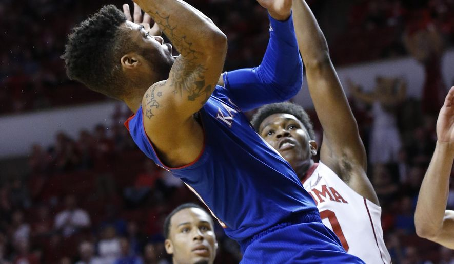 Kansas guard Frank Mason III, left, shoots in front of Oklahoma guard Kameron McGusty, right, during the first half of an NCAA college basketball game in Norman, Okla., Tuesday, Jan. 10, 2017. (AP Photo/Sue Ogrocki)
