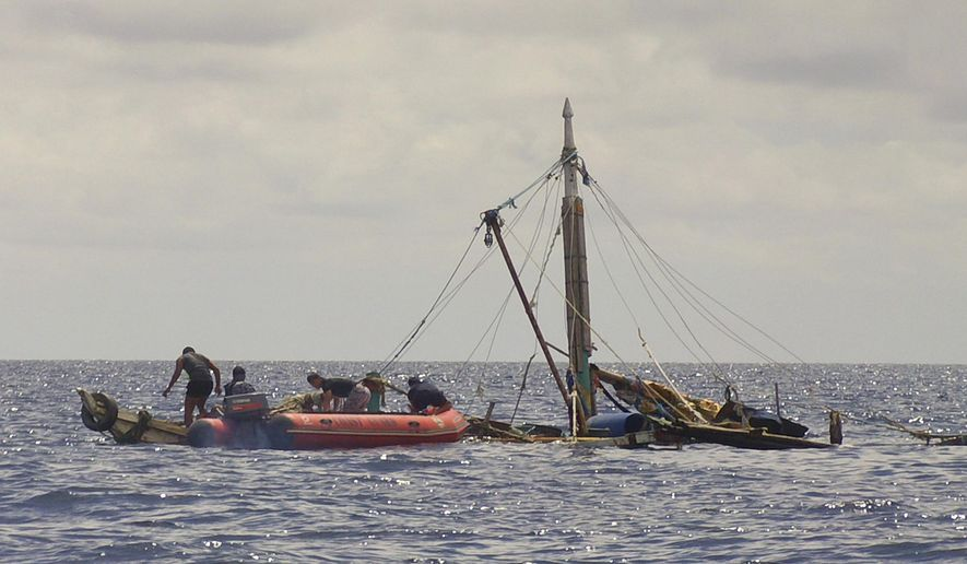 In this photo provided by the Philippine Coast Guard, members of the Philippine Coast Guard, left, approach the almost sunken fishing boat of Filipino fishermen who were killed by suspected pirates in waters near Zamboanga City, southern Philippines Tuesday, Jan. 10, 2017. Several Filipino fishermen were killed after a group of suspected pirates boarded a fishing boat in southern Philippine waters and strafed the crew, officials said Tuesday. (Philippine Coast Guard via AP)