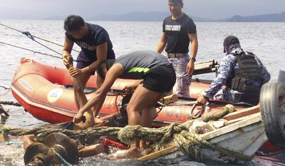 In this photo provided by the Philippine Coast Guard, members of the Philippine Coast Guard pick up one of the bodies of Filipino fishermen who were killed by suspected pirates on their fishing boat in waters near Zamboanga City, southern Philippines Tuesday, Jan. 10, 2017. Several Filipino fishermen were killed after a group of suspected pirates boarded a fishing boat in southern Philippine waters and strafed the crew, officials said Tuesday. (Philippine Coast Guard via AP)