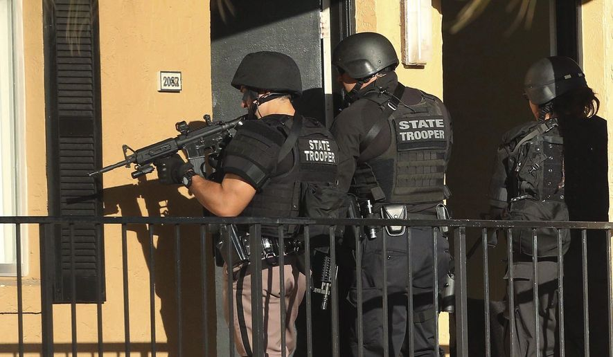Law enforcement officers conduct a door-to-door search at an apartment complex in Orlando, Fla., Monday, Jan. 9, 2017. An Orlando police sergeant was shot and killed Monday after approaching a suspect wanted for questioning in the murder of his pregnant ex-girlfriend, and a second law enforcement officer was killed in a motorcycle crash while responding to the massive manhunt for the suspect. (Stephen M. Dowell/Orlando Sentinel via AP)