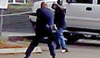 FILE - In this Sept. 27, 2016 file image made from from bystander video provided by the El Cajon Police Department, Alfred Olongo, right, is seen pointing what was later determined to be a bulky electronic cigarette device at El Cajon, Calif., police officer Richard Gonsalves during a confrontation at an El Cajon strip mall. Moments later Olongo was shot and killed. San Diego County District Attorney Bonnie Damais announced Tuesday, Jan. 10, 2017, that no criminal charges will be filed against Gonsalves. (El Cajon Police Department/San Diego County District Attorney's Office via AP, File)