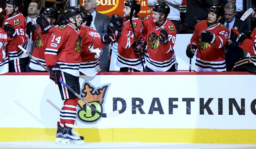 Chicago Blackhawks left wing Richard Panik (14) celebrates his goal against the Detroit Red Wings with teammates during the first period of an NHL hockey game on Tuesday, Jan. 10, 2017, in Chicago. (AP Photo/Matt Marton)