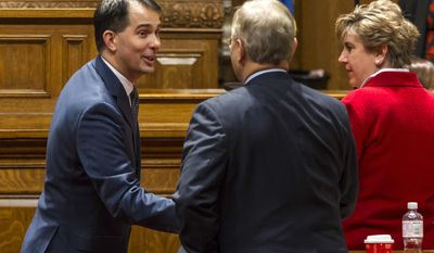 Wisconsin Gov. Scott Walker, center, shakes hands with Minority Leader Peter Barca, D-Kenosha, after Walker's state of the state address to a joint session of the Legislature in the Assembly chambers at the state Capitol on Tuesday, Jan. 10, 2017, in Madison, Wis. (AP Photo/Andy Manis)