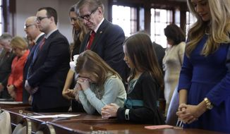 Megan LeGrand, center, and Lindsay LeGrand, right, pray as they stand with their grandfather, Rep. Phil Stephenson, R-Wharton, during the opening of the 85th Texas Legislative session at the Texas State Capitol, Tuesday, Jan. 10, 2017, in Austin, Texas. (AP Photo/Eric Gay)