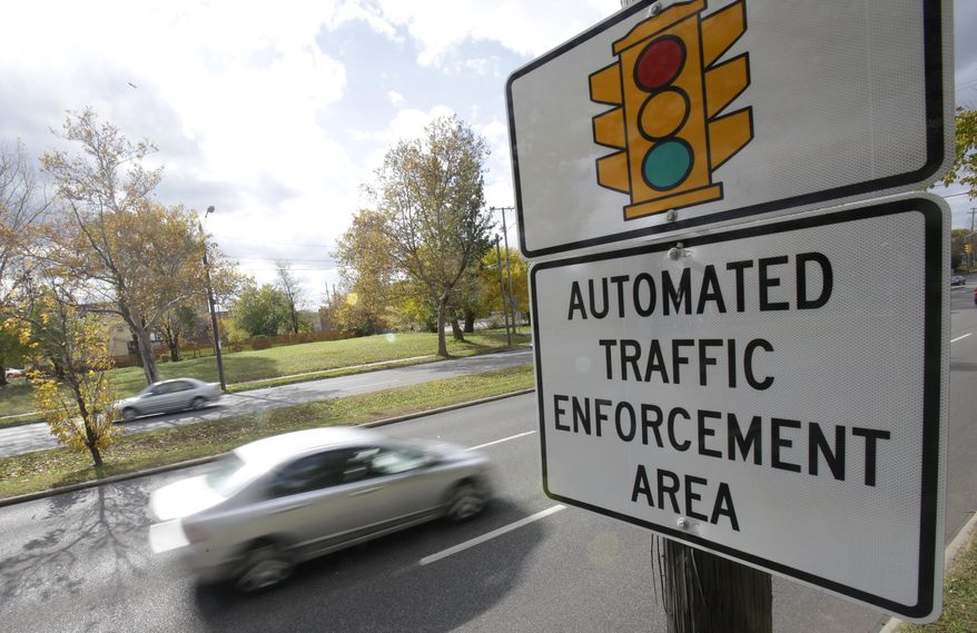 In this Oct. 29, 2014, file photo, motorists drive past a sign warning of upcoming traffic cameras in Cleveland. (AP Photo/Tony Dejak, File)