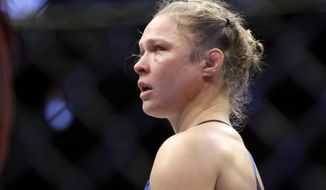 "FILE - In this Dec. 30, 2016, file photo, Ronda Rousey stands in the cage after Amanda Nunes forced a stoppage in the first round of their women's bantamweight championship mixed martial arts bout at UFC 207 in Las Vegas. Rousey broke her silence since the fight by posting a quote about rebuilding from ""rock bottom"" on Instagram Monday, Jan. 9, 2017. (AP Photo/John Locher, File)"