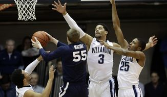 Xavier's J.P. Macura (55) goes up for a shot against Villanova's Mikal Bridges (25), Josh Hart (3) and Jalen Brunson (1) during the first half of an NCAA college basketball game, Tuesday, Jan. 10, 2017, in Villanova. (AP Photo/Matt Slocum)