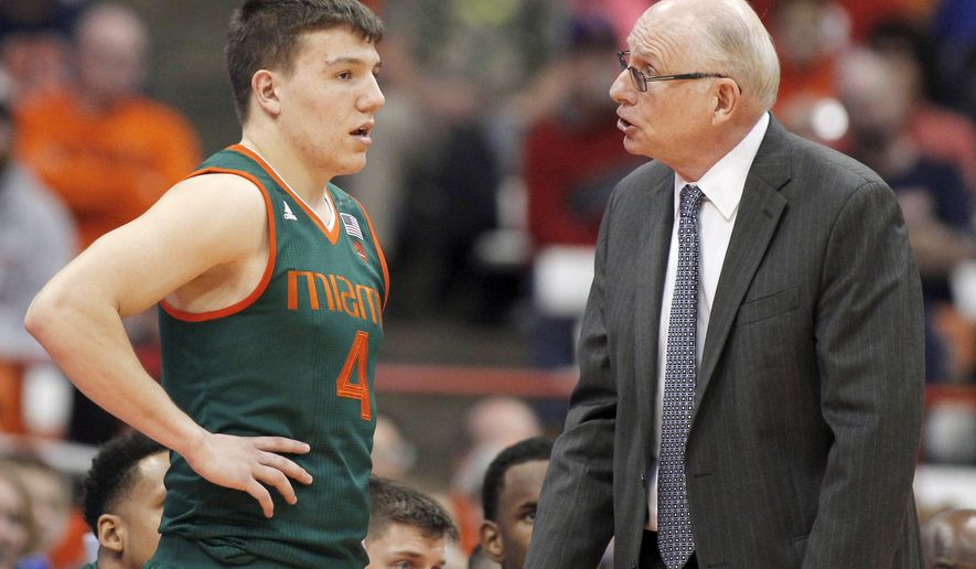 FILE - In this Wednesday, Jan. 4, 2017, file photo, Miami head coach Jim Larranaga, right, talks with Dejan Vasiljevic, left, late in the second half of an NCAA college basketball game against Syracuse in Syracuse, N.Y. Larranaga is looking for a turnaround. His young team will try to bounce back from an ugly loss at Syracuse when it hosts No. 20 Notre Dame on Thursday. Jan. 12. (AP Photo/Nick Lisi, File)