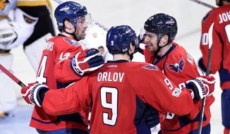 Washington Capitals right wing Justin Williams (14) celebrates his goal with center Evgeny Kuznetsov (92), of Russia, (92) and defenseman Dmitry Orlov (9), of Russia, (9) during the third period of an NHL hockey game against the Pittsburgh Penguins, Wednesday, Jan. 11, 2017, in Washington. The Capitals won 5-2. (AP Photo/Nick Wass)